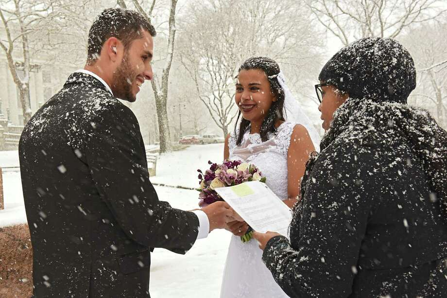 Alceir Dossantos and his bride Adriana get say their vows as they get married in front of the State Capitol on Thursday, Dec. 29, 2016 in Albany, N.Y. The couple, originally from Brazil, came all the way to Albany from Florida, where they live now, to get married in the snow. (Lori Van Buren / Times Union) Photo: Lori Van Buren