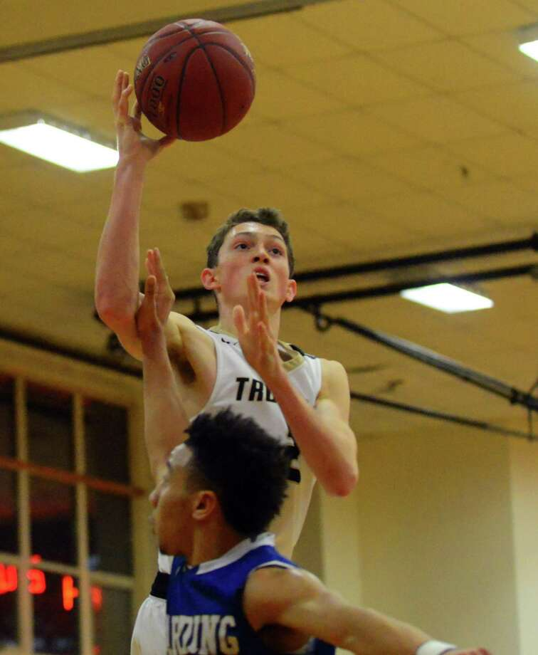 Trumbull's John Lynch lays up the ball as Harding's Justin Sheffield blocks during the first round of Merit Insurance Classic boys basketball tournament action in Stratford, Conn., on Thursday Dec. 29, 2016. Photo: Christian Abraham / Hearst Connecticut Media / Connecticut Post