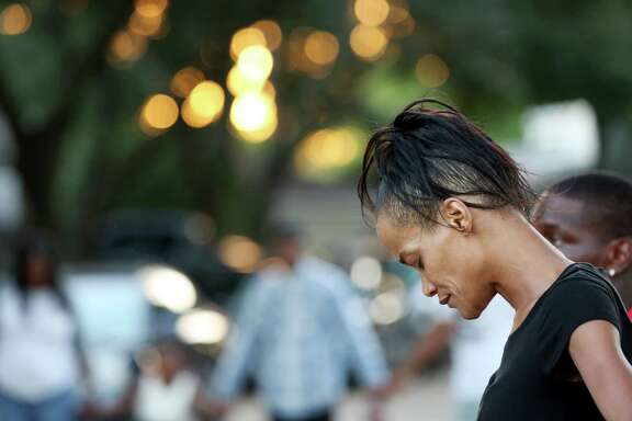 A woman prays in a circle during a united prayer outside of Casey Brown's house to seek justice for Brown Sunday, Oct. 16, 2016, in Houston. Brown is the shooting victim of an off-duty police officer over a dog dispute.