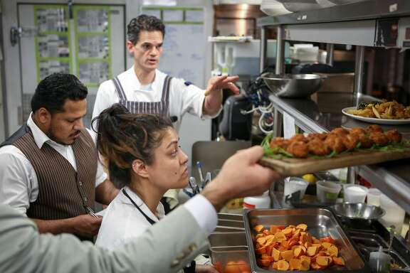 (left to right) David Baltodano, Calvin Pafford, and Myrhissa Bautista are busy in the kitchen during dinner service at Bluestem on Tuesday, November 22, 2016 in San Francisco, Calif.