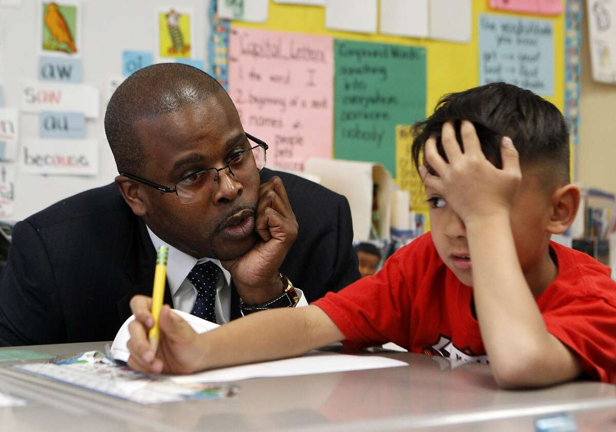 Former Superintendent of the Oakland School District, Antwan Wilson, speaks with first grader Logan McMahon during a tour of the Lincoln Elementary school along with Mayor Libby Schaaf in Oakland, Calif., on Thursday, March 24, 2016.