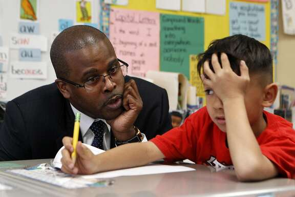 Superintendent of the Oakland School District, Antwan Wilson, speaks with first grader Logan McMahon during a tour of the Lincoln Elementary school along with Mayor Libby Schaaf in Oakland, Calif., on Thursday, March 24, 2016. The tour highlights the school's success in closing the achievement gap, as can be seen in the Education Equality Index.