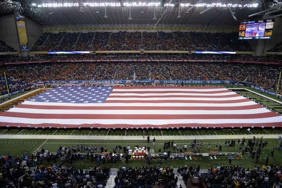 A giant American flag is unfurled during the national anthem before the Alamo Bowl, Thursday, Dec. 29, 2016, at the Alamodome in San Antonio. (Darren Abate/For the Express-News)