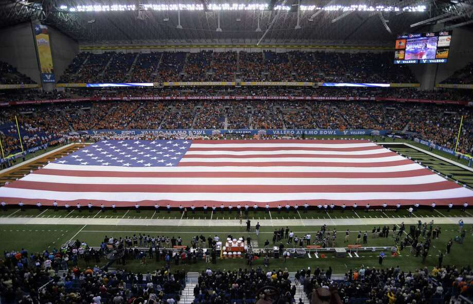 A giant American flag is unfurled during the national anthem before the Alamo Bowl, Thursday, Dec. 29, 2016, at the Alamodome in San Antonio. Selrico Services was awarded a custodial contract for the Alamodome in May 2017. Photo: Darren Abate /San Antonio Express-News