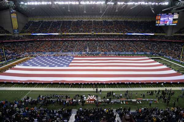 A giant American flag is unfurled during the national anthem before the Alamo Bowl, Thursday, Dec. 29, 2016, at the Alamodome in San Antonio. Selrico Services was awarded a custodial contract for the Alamodome in May 2017.