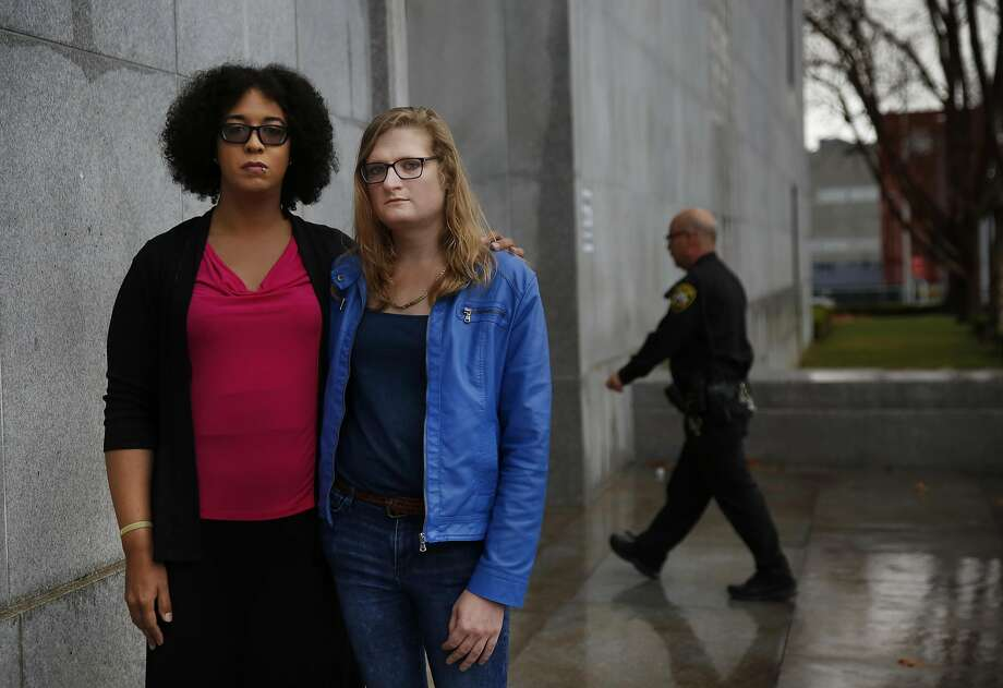 Athena Cadence (left) stands with her partner, Sophia Lionberger, outside of the S.F. Hall of Justice last month. Photo: Leah Millis, The Chronicle
