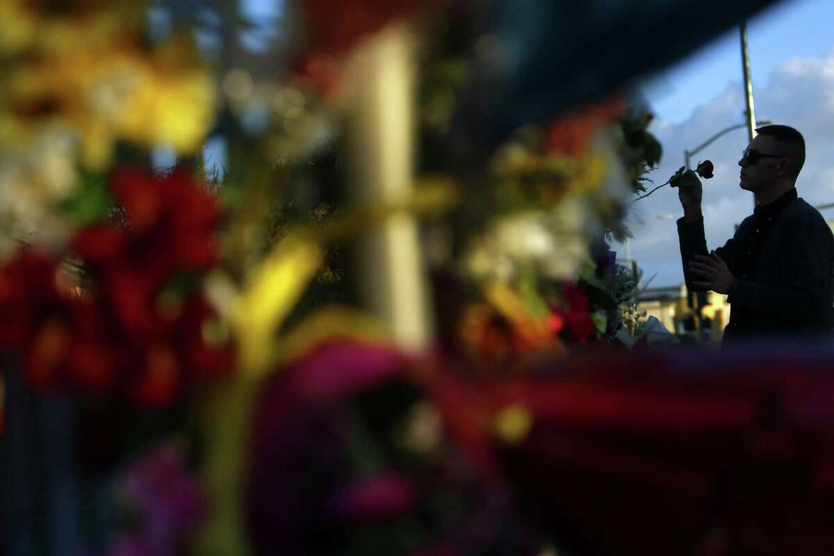December 6, 2016 - David Sisak places a rose at an E. 12th Street memorial in memory of his friends Johnny Igaz, Amanda Kershaw and Chelsea Dolan during the aftermath of the Ghost Ship fire in Oakland, California. Mr. Sisak had a ticket to the December 2nd show at the warehouse but decided to not attend.