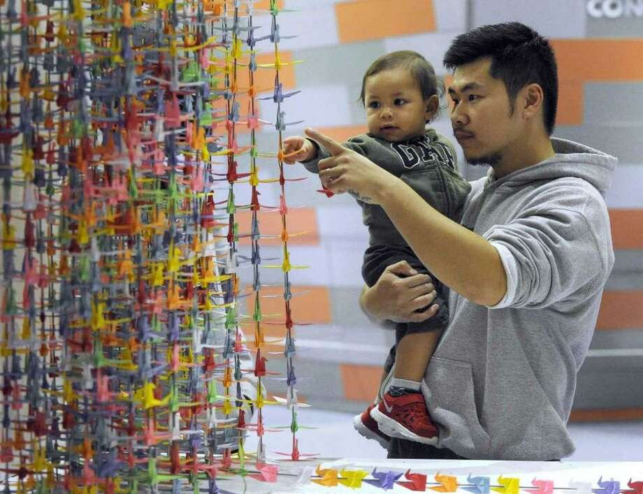 Nghiep Luu, 29, and son Aiden, 15 months, look at Luu's origami crane exhibit as it is being installed in the lobby of the Visual & Performing Arts Center at Western Connecticut State University in November. Photo: / Carol Kaliff