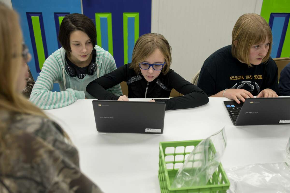 From left: 12-year-old Sophia Waugh, 12-year-old Ellarie Ryals and 13-year-old Marissa Berghuis, all of Midland, look at designs that have been printed on a 3D printer during The ROCK Center for Youth Development's Winter Break Blitz at the Greater Midland Community Center Thursday. AmeriCorps Volunteer In Service to America member Ben Martinson brought his 3D printer to show students how it works and how it turns 2D design into 3D objects as part of The ROCK's new STEM program, ROCKit.