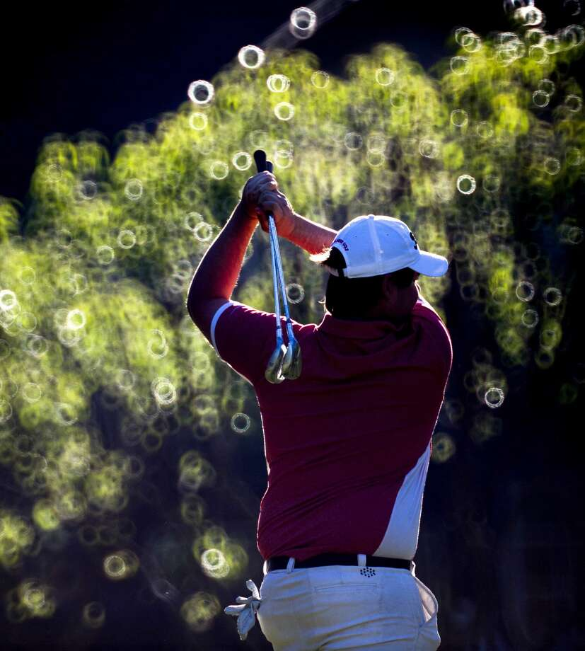 In this photo, taken with a Nikkor 500mm f8 mirror lens, The Woodlands' Josh Drachman warms up on the putting green during the final day of the District 16-6A boys golf championship at High Meadow Ranch Golf Course Tuesday, April 5, 2016, in Magnolia, Texas. Photo: Jason Fochtman/Houston Chronicle