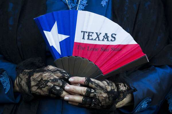Pat Spackey holds a fan with the design of the Texas flag during a statue unveiling at the Spirit of Texas Bank's new location on Lake Front Circle Tuesday, Nov. 15, 2016, in The Woodlands. The statue, created by Craig Campobella, is entitled 'New Beginnings' and features Stephen F. Austin and Jose Antonio Navarro. Spackey is a descendant of Charles Stewart, the designer of the Texas flag.