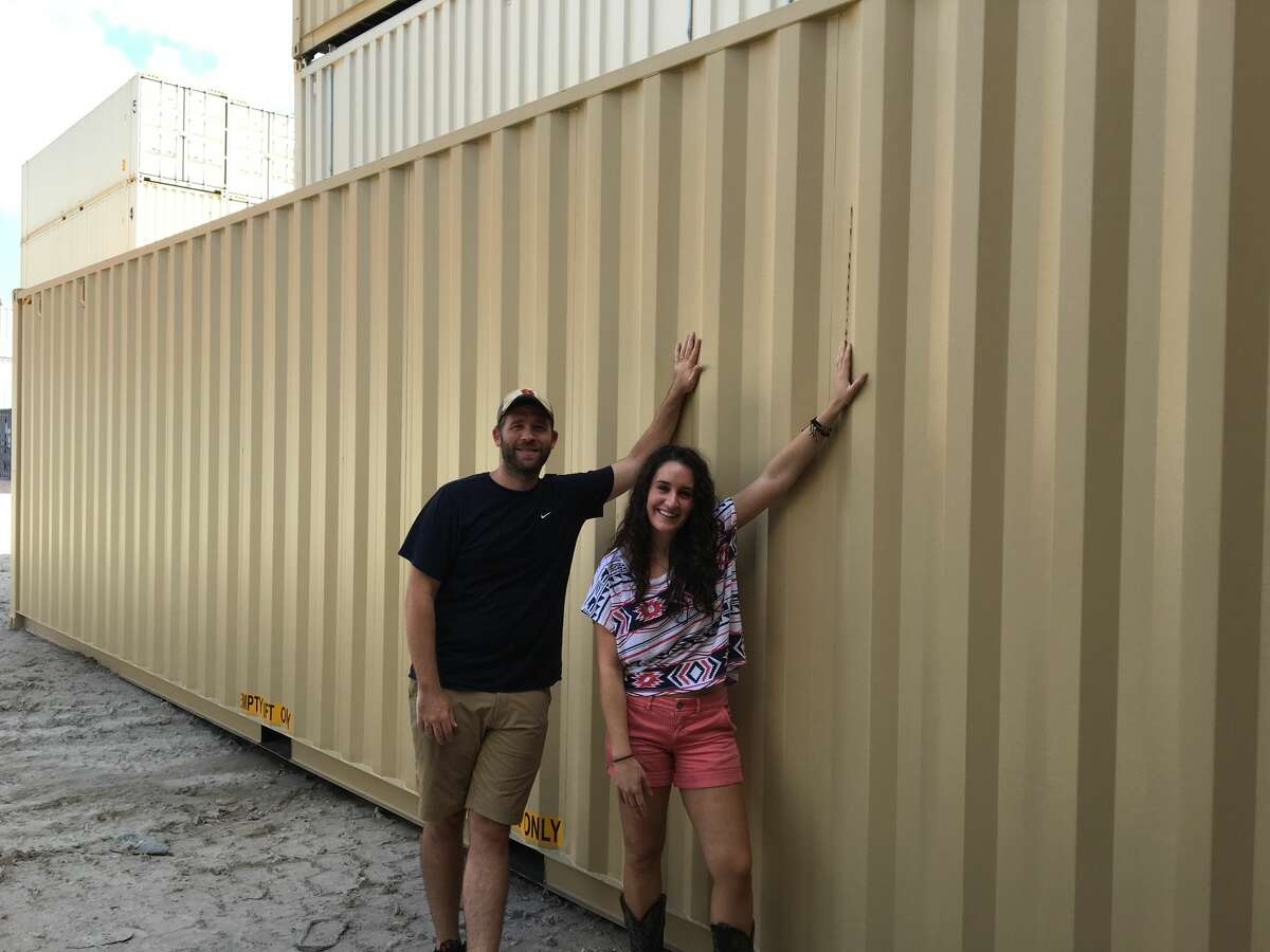 Emily Flowers and her brother-in-law Jon Meier pick out the shipping container that will become her home.