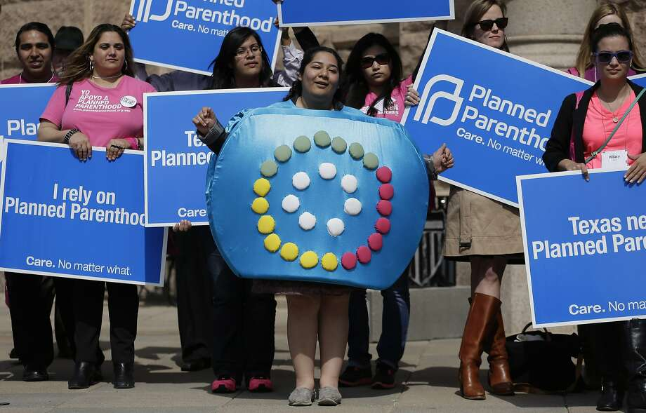 Alyssa Travino, center, of Edinburg, Texas, wears a birth control bill box costume during a Planned Parenthood rally on the steps of the Texas Capitol,Thursday, March 7, 2013, in Austin, Texas. (AP Photo/Eric Gay) Photo: Eric Gay, Associated Press