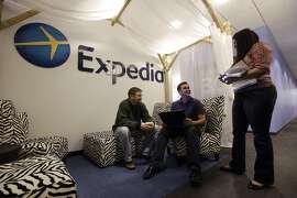 FILE - In this Tuesday, Jan. 15, 2013, file photo, Expedia analytics team workers Mike Brown, left, Saurin Pandya and Prashanti Tata chat in an alcove set up for employees, in Bellevue, Wash. The American Hotel & Lodging Association on Thursday, Aug. 6, 2015 issued a statement announcing its opposition to the proposed combination of travel booking sites Expedia and Orbitz, saying that the deal would mean higher prices for vacationers and larger fees for hotel owners.  (AP Photo/Elaine Thompson, File)