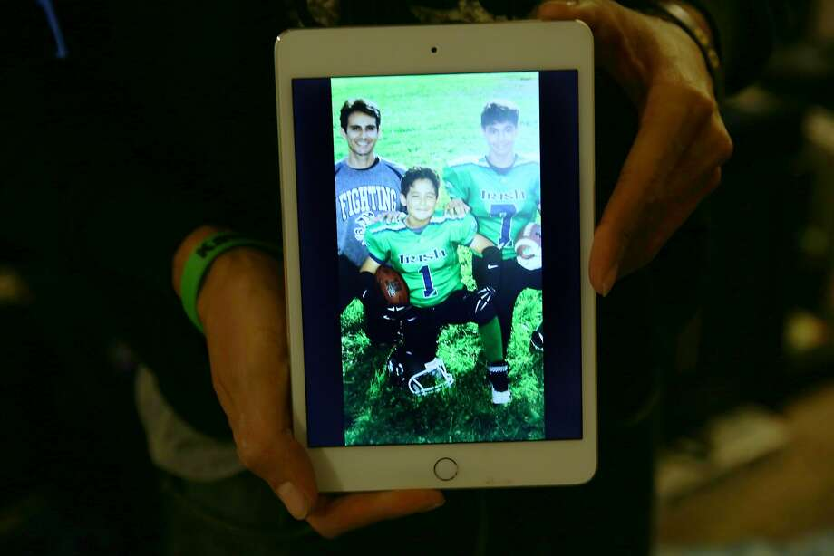 Daniel Espinoza shows a photo of himself with song Daiemeon (center) and Daniel. He volunteers with the boys' football team. He badly hurt his thumb riding skateboard with his sons and missed work for weeks. Photo: Santiago Mejia, The Chronicle
