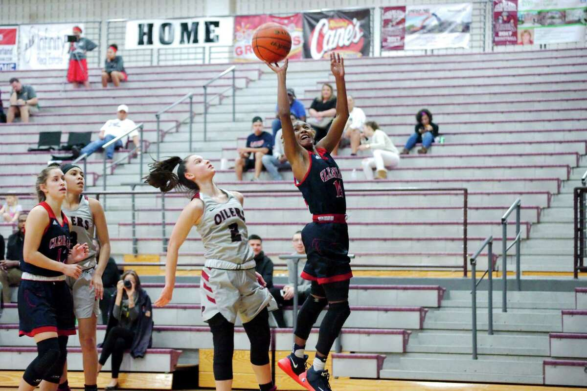 Clear Lake guard Courtnee LaBarrie drives past Pearland's Macey Braswell to the basket in a non-district girls' basketball game.
