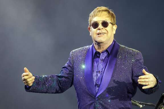 """FILE- In this Thursday, May 26, 2016, file photo, musician Elton John performs during a show in Tel Aviv. Elton John is giving filmmakers a chance to create music videos for his 1970s hits that were released before music videos were popular. The English singer announced Monday, Dec. 12, 2016, in celebration of he and songwriting partner Bernie Taupin's 50th anniversary, that he's launching a competition for aspiring video creators to make music videos for """"Rocket Man,"""" """"Tiny Dancer"""" and """"Bennie and the Jets."""" (AP Photo/Dan Balilty, File)"""
