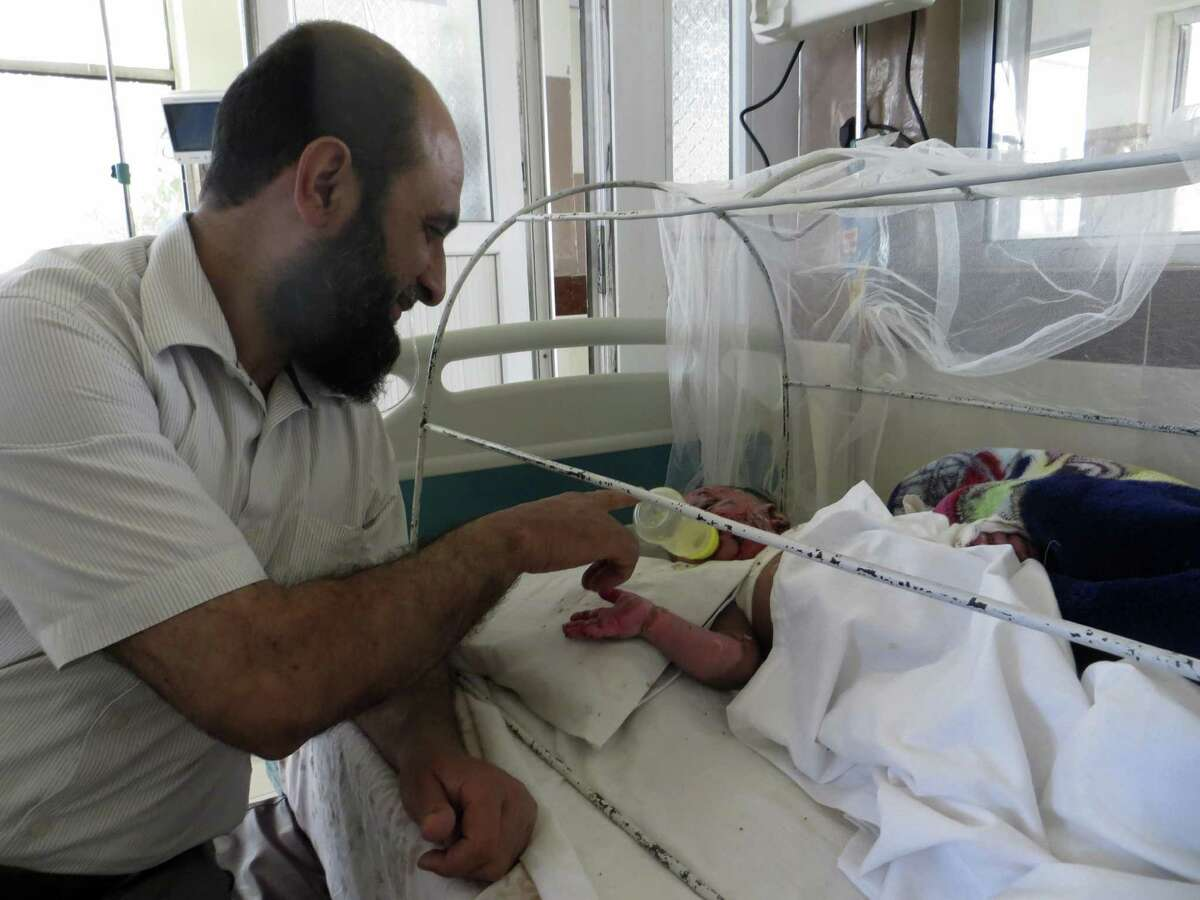 Dr. Habib Rahman, a pediatric burn surgeon at the Indira Gandhi Institute of Child Health in Kabul, checks on a 6-month-old boy who was brought to the hospital after he was scalded by hot water. Rahman?'s patients, most of whom are injured in household accidents, come to the hospital from across Afghanistan