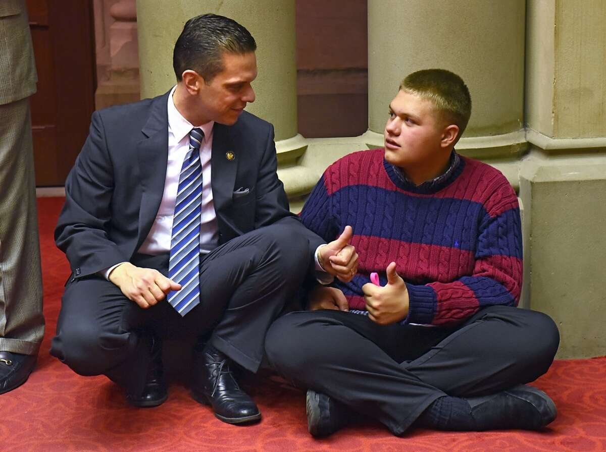 New York Assemblyman Angelo Santabarbara gives a thumbs up to his son Michael who reciprocates after being sworn in for another term administered by Congressman Paul Tonko in the Assembly Chamber of the State Capitol on Thursday, Dec. 29, 2016 in Albany, N.Y. Michael has autism and his father was telling him he did a great job standing on the podium in front of such a large crowd. (Lori Van Buren / Times Union)