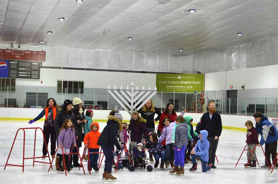Celebrants pose for pictures around the menorah at the Chabad of New Canaan and Darien's Hanukkah skating party at Darien Ice Rink, Wednesday, Dec. 29, 2016, in Darien, Conn. Photo: Jarret Liotta / For Hearst Connecticut Media / Darien News Freelance