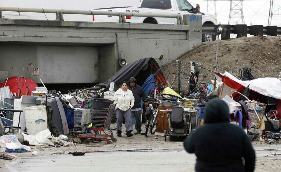 A man and a woman walk through a homeless camp alongside the San Gabriel River beneath the State Route 90 Freeway in El Monte, Calif. A reader addresses the housing problem in America. Photo: Nick Ut /Associated Press / Copyright 2016 The Associated Press. All rights reserved. This material may not be published, broadcast, rewritten or redistribu