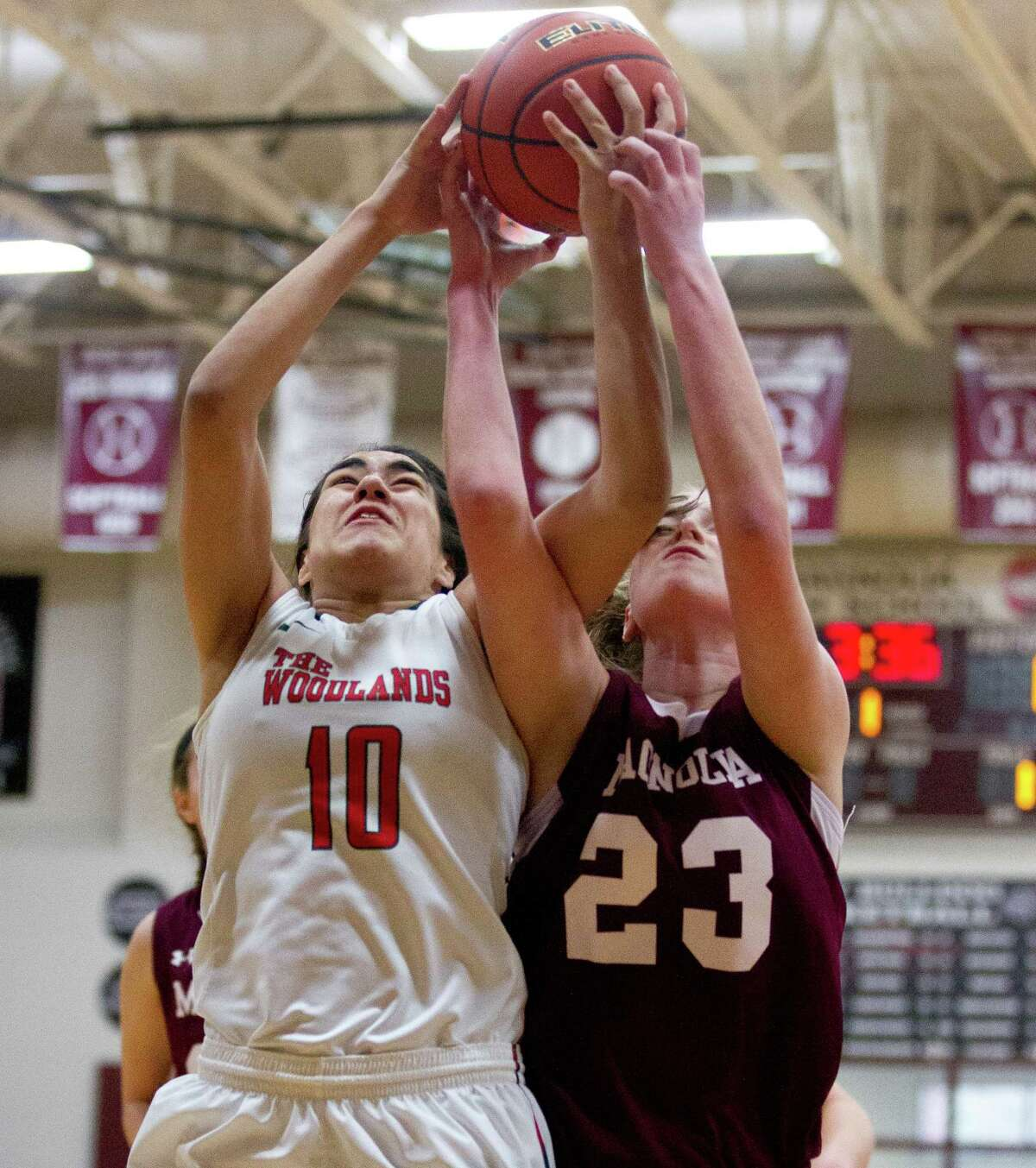 The Woodlands forward Luisa De La Rosa (10) and Magnolia forward Alexus Wykoff (23) battle for a rebound during the first quarter of a high school girls basketball game at the Magnolia Holiday Hoop Fest Friday, Dec. 30, 2016, in Magnolia.