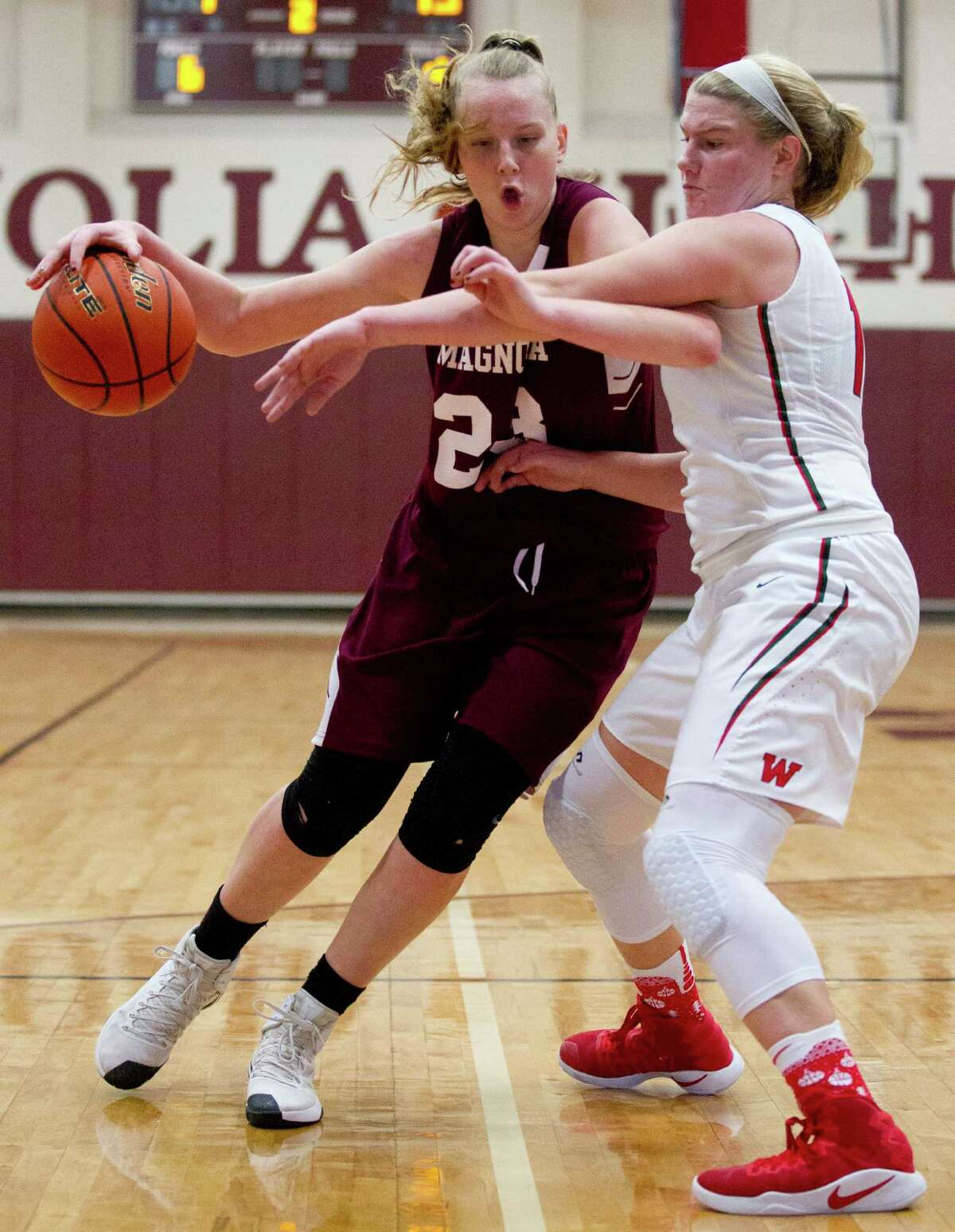 Magnolia forward Alexus Wykoff (23) works inside as The Woodlands forward Madison Morton (15) defends during the second quarter of a high school girls basketball game at the Magnolia Holiday Hoop Fest Friday, Dec. 30, 2016, in Magnolia.