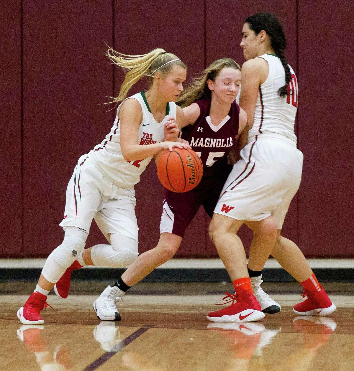 The Woodlands guard Sarah Butterfield (12) drives past Magnolia guard Abby Gibson (15) after a pick by forward Luisa De La Rosa (10) during the second quarter of a high school girls basketball game at the Magnolia Holiday Hoop Fest Friday, Dec. 30, 2016, in Magnolia.