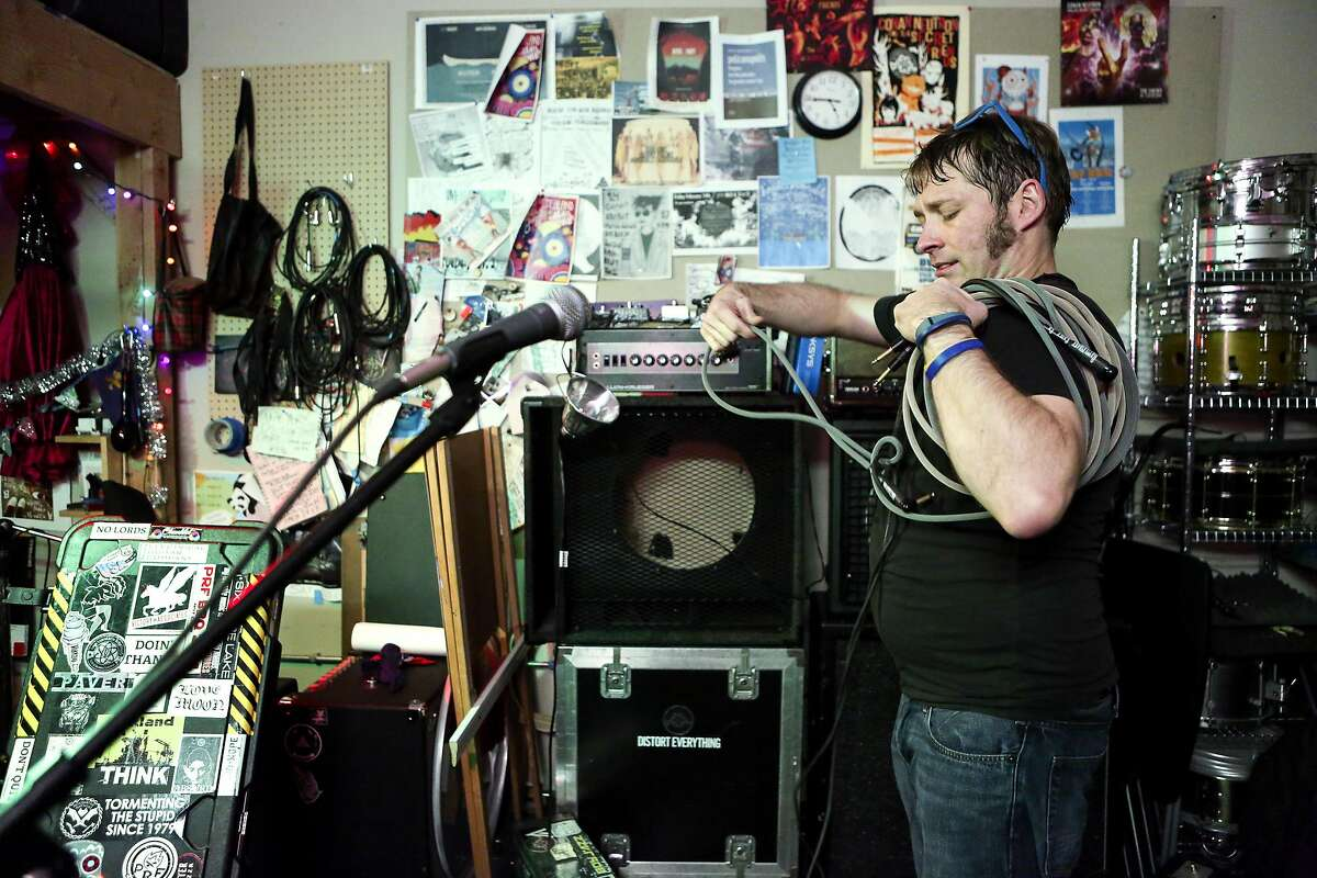 Conan Neutron sets up his electric guitar in his band's practice space which is in a warehouse in West Oakland on Friday, December 30, 2016.