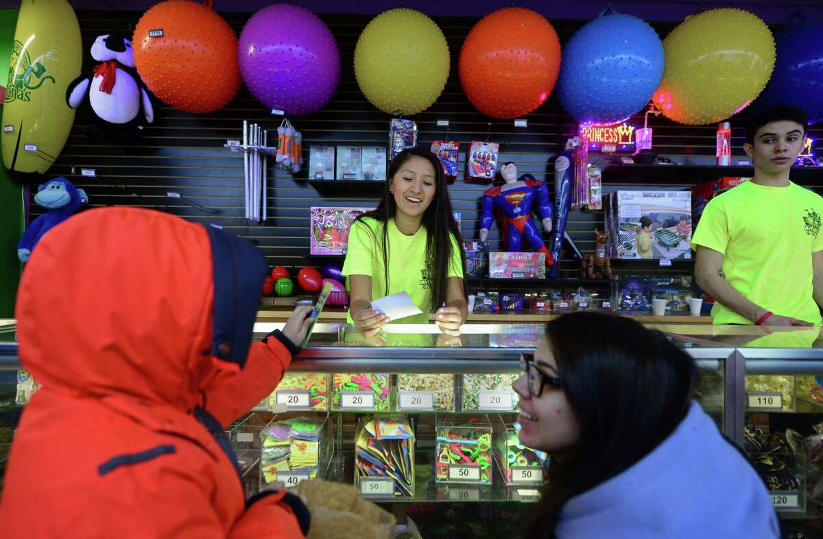 Norwalk High School students Denise Mejia and Luis Guerra help customers Valeria Maya and her son, Samuel Ospina, 6, on Friday at My Three Sons in Norwalk . As of the first of the new year, minimum wage will rise to $10.10 per hour. The 50 cent increase is the third in a three-year-process to raise wages from $8.70.