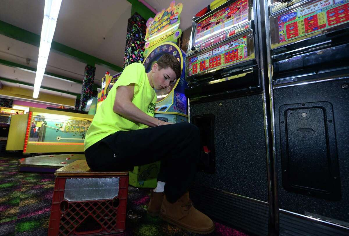 Danny Frattoroli works to fix a slot machine Friday at My Three Sons in Norwalk . As of Jan. 1, minimum wage will rise to $10.10 per hour. The 50 cent increase is the third in a three-year-process to raise wages from $8.70. While it is only a half-dollar more per hour, over a 40-hour workweek, that can add up to an extra $20 in the pocket of a full-time minimum wage worker, which some say will make a world of a difference.