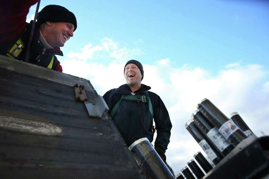 Jon Bergson, left, and Scott Streeper, members of the pyrotechnic crew, install fireworks atop the Space Needle in preparation for a New Year's show that will welcome in 2017, Friday, Dec. 30, 2016. Photo: SEATTLEPI.COM / SEATTLEPI.COM