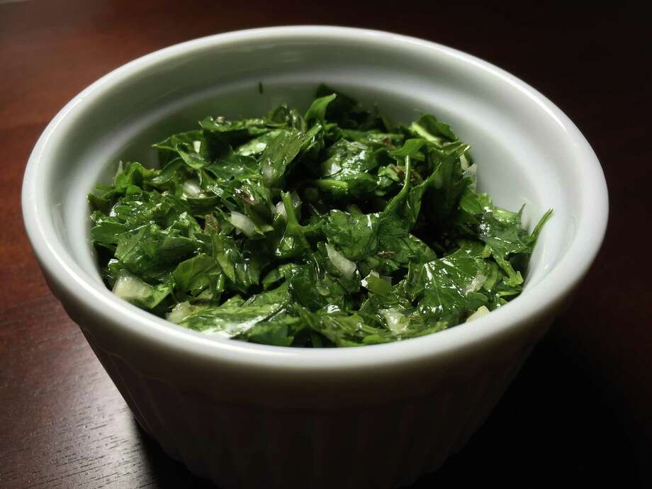 Chimichurri, a mixture of minced parsley, onion, olive oil, vinegar and oregano, is a classic Argentinian accompaniment for grilled meats. Photo: Edmund Tijerina, Staff / San Antonio Express-News / San Antonio Express-News