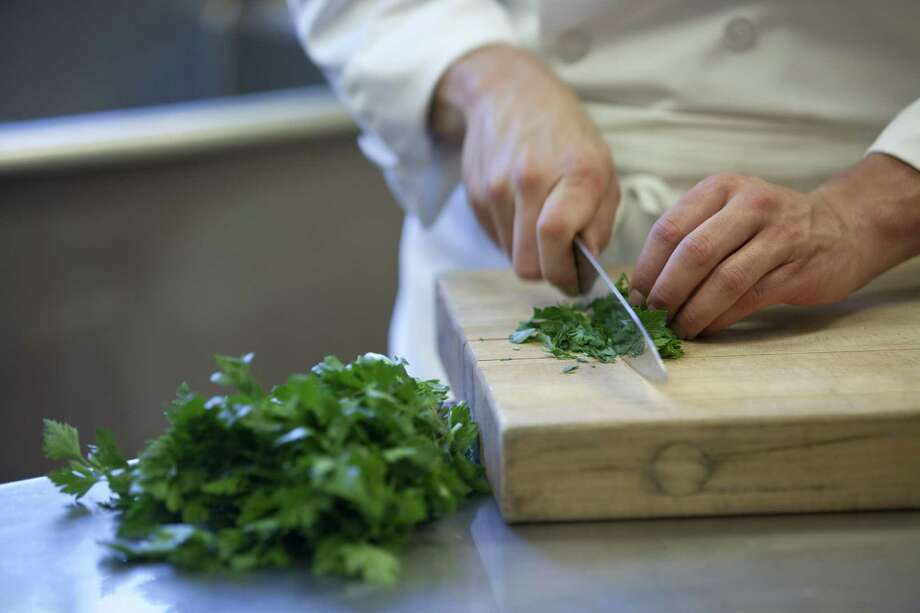 When chopping parsley by hand, be sure to curl your fingers under so you don't cut yourself. Keeping your knives sharp also will reduce the chances of cutting yourself. Photo: Anne Rettig /Culinary Institute Of America / ©2010 Anne Rettig/The Culinary Institute of America