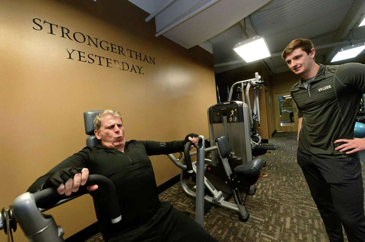 Stuart Hazelwood works out under the watchful eye of his trainer Jake Parton on Monday, Dec. 26, at Anytime Fitnesss on Westport Avenue in Norwalk. The end of the year has many people making fitness based New Year's resolutions.