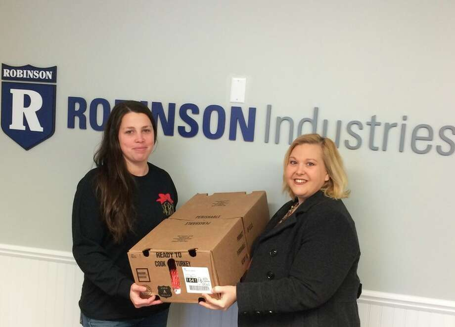 Photo provided Amber from Robinson Industries hands the turkeys off to Stephanie Buffman from United Way of Clare and Gladwin Counties, who delivered the turkeys to New Dawn Shelter.