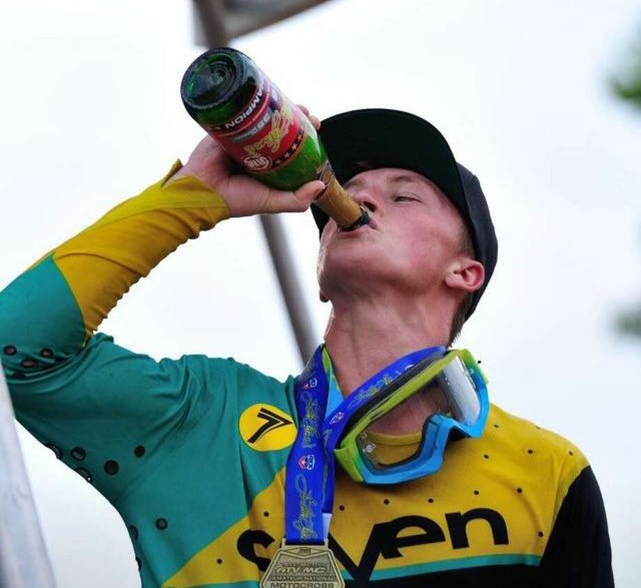 Wilson Fleming sips some champagne after winning the 400B limited title at the Loretta Lynn AMA Amateur National Motocross Championship in Hurrican Mills, Tenn. this past August. Photo: Contributed Photo / New Canaan News contributed