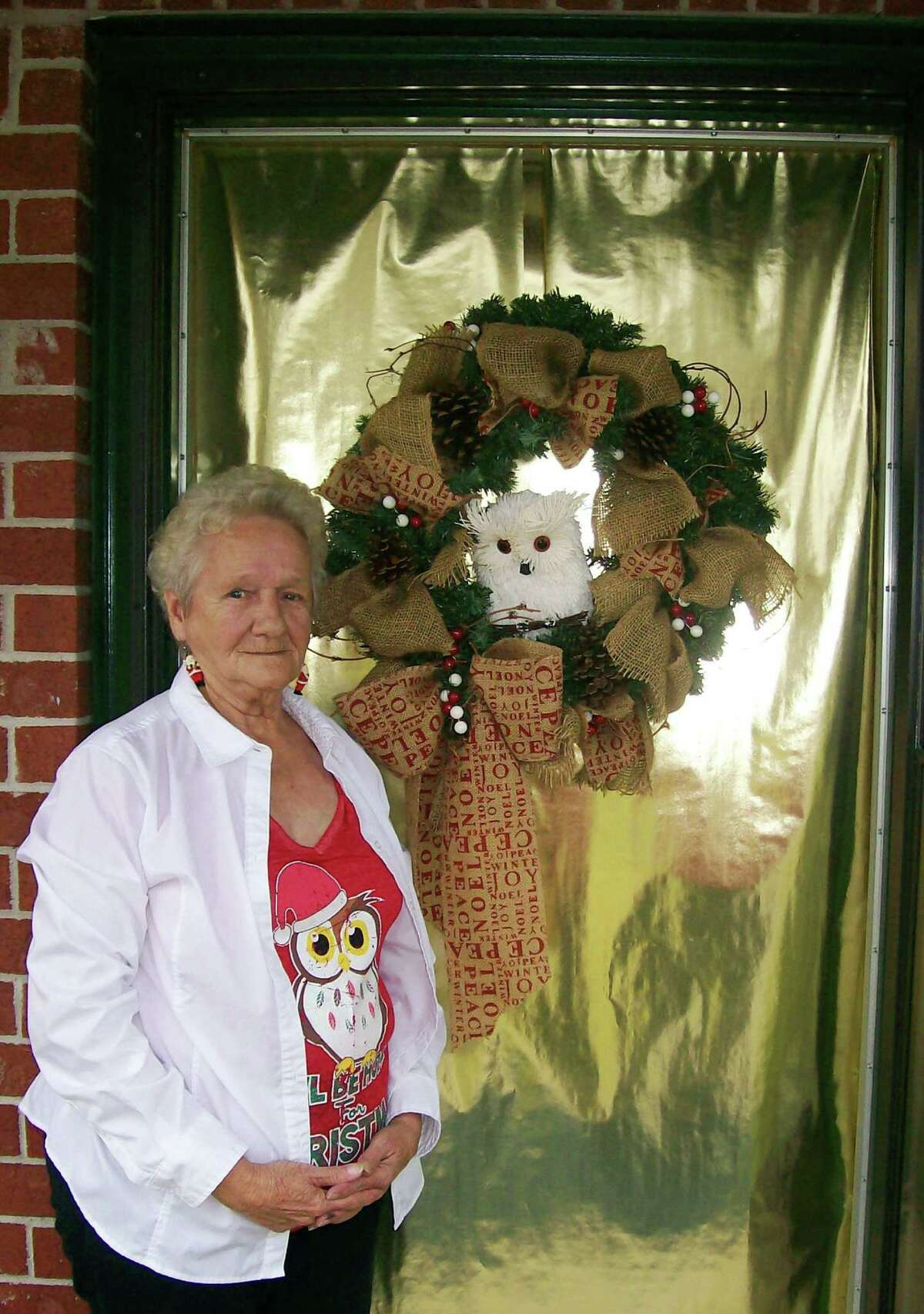 Second place in Azalea Terrace's door decorating contest for the Christmas season ended in a three-way tie. Pictured is Dixie Vansant and her gold door decorated with a wreath and owl. The other second-place winners were Arletta Bertrand and Judith Rucker.