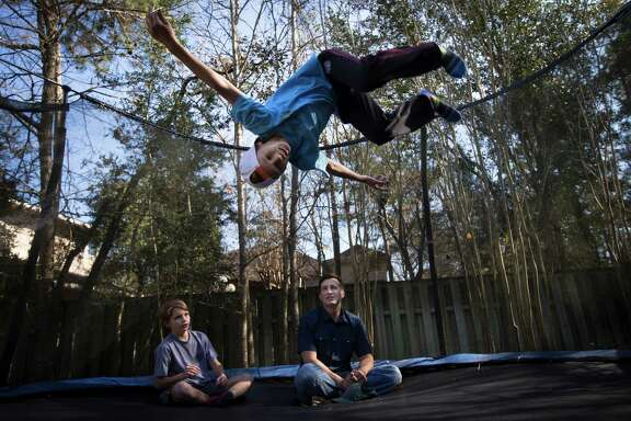 Benner Grau, 11, and his father, David, watch his twin brother, Hayden, flip in the air on a sunny day at home in The Woodlands. David works in Dallas and only has weekends to spend with his family.