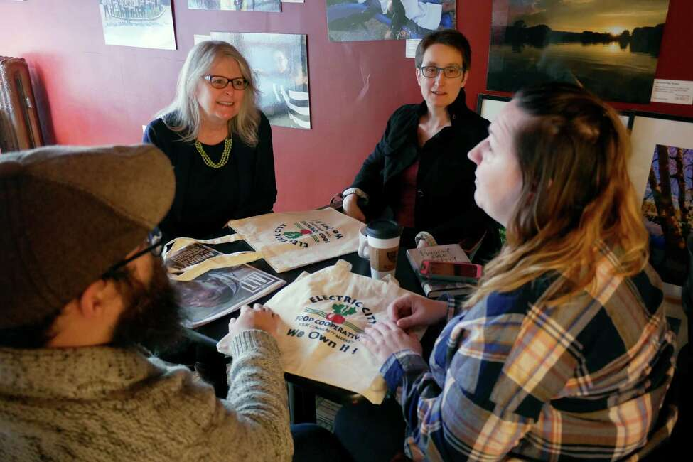 Kat Marsh Wolfram, background left, the board president of the Electric City Food Cooperative, meets with new members of the coop, Sean Britten, foreground left, of Schenectady, his girlfriend Lisa Sharp, foreground right, of Schenectady and Cris Merray of Delmar at the Happy Cappuccino on Wednesday, Dec. 28, 2016, in Schenectady, N.Y. (Paul Buckowski / Times Union)