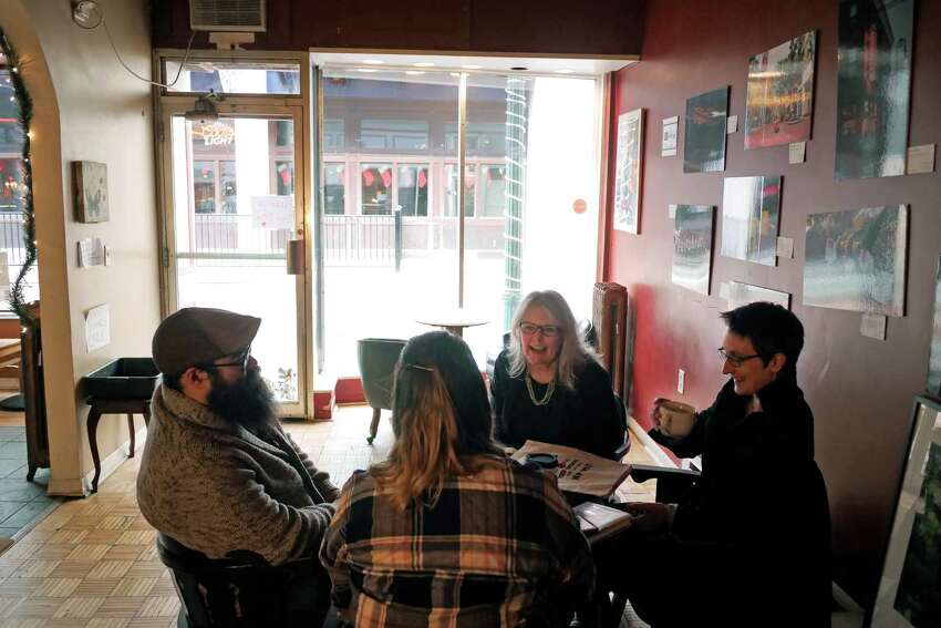 Kat Marsh Wolfram, third from left, the board president of the Electric City Food Cooperative, meets with new members of the coop, Sean Britten, left, of Schenectady, his girlfriend Lisa Sharp, foreground right, of Schenectady and Cris Merray, right, of Delmar at the Happy Cappuccino on Wednesday, Dec. 28, 2016, in Schenectady, N.Y. (Paul Buckowski / Times Union)