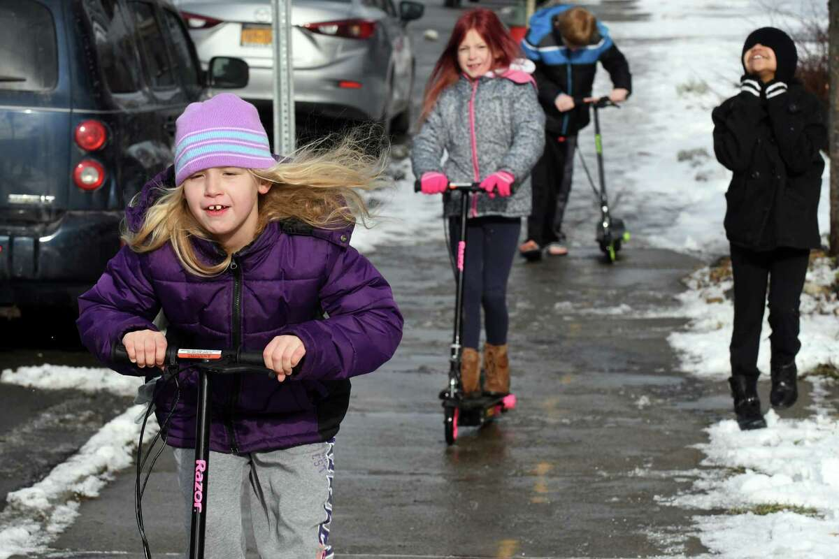 Nine-year-old Brianna St. Andrews, left, rides her electric scooter she received for Christmas with her friends down 15th Street on Friday Dec. 30, 2016 in Troy, N.Y. (Michael P. Farrell/Times Union)