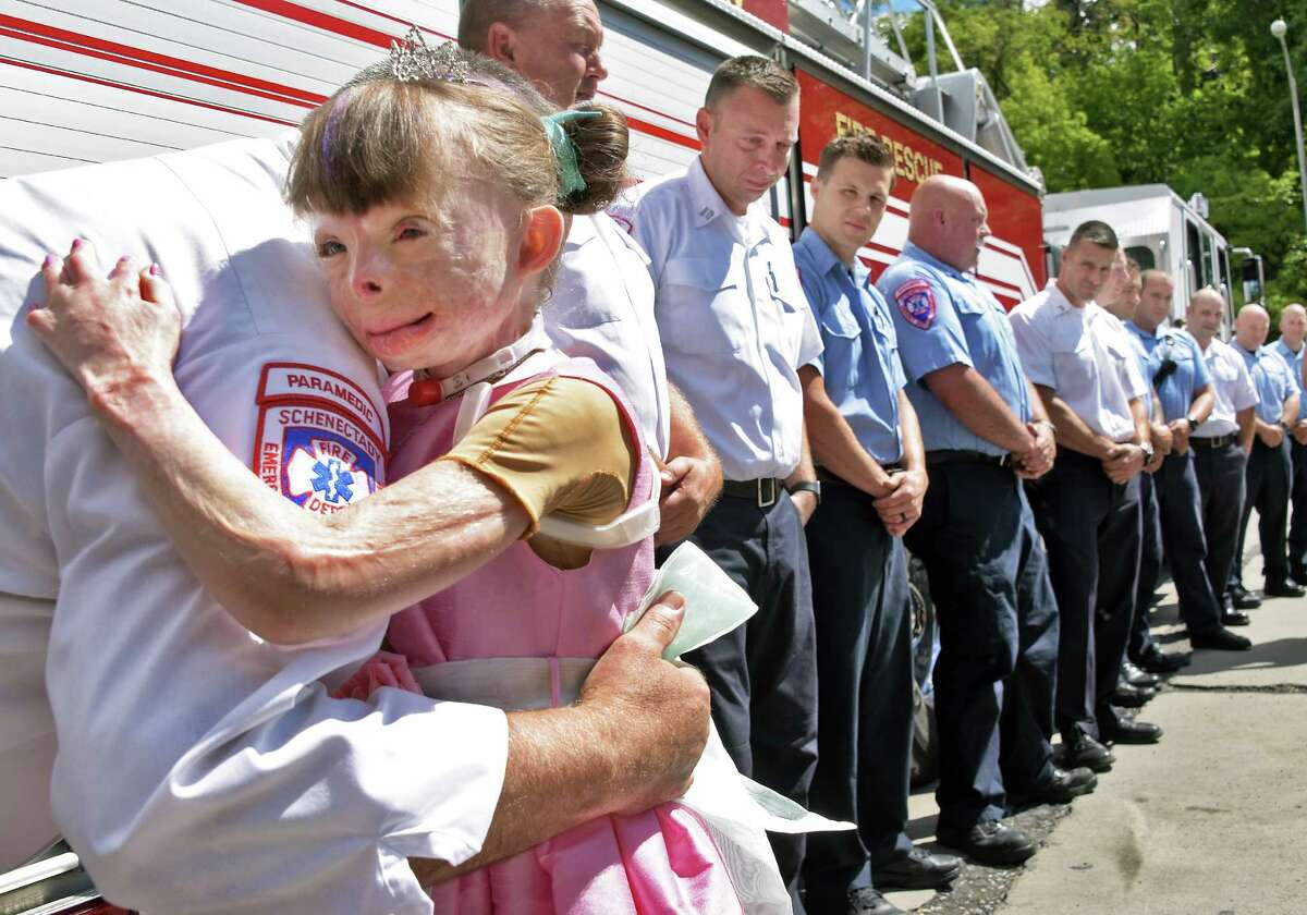 Nine-year-old arson fire survivor Sa'fyre Terry hugs members of the Schenectady Fire Dept. during her birthday visit to Schenectady FD Station 1 Friday Sept. 2, 2016 in Schenectady, NY. (John Carl D'Annibale / Times Union)