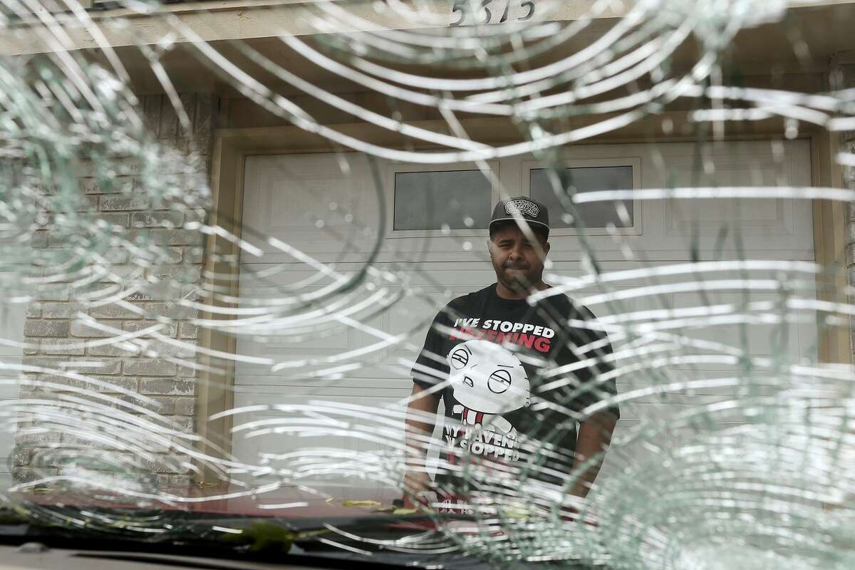 FILE - In this April 13, 2016, file photo, Rodney Rodriguez checks the damage to his 2008 Ford Escape in the Woodlake neighborhood in San Antonio, after a severe hailstorm hit the area the night before. The Insurance Council of Texas says a hailstorm that hit the San Antonio area last week proved to be the costliest in Texas history, with damage estimated at nearly $1.4 billion. (Jerry Lara/San Antonio Express-News via AP, File) MAGS OUT NO SALES SAN ANTONIO OUT