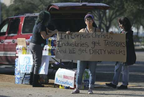 Dorothy Pena holds up a sign protesting the possible water contamination that took place in Corpus Christi in mid-December. For three days, much of the city of 320,000 people had to rely on bottled water for all uses, including washing and cooking, after a possible contamination event at an Ergon emulsifier manufacturing plant that is leased from Valero Energy Corp.