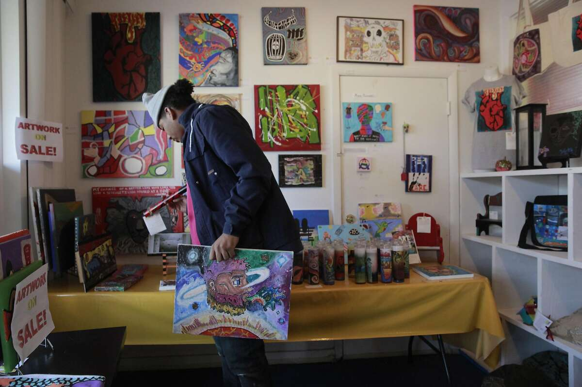 Sean McCready holds a piece of art he created while looking through the artwork for sale at their office in Berkeley, California, on Friday December 30, 2016. Sally Hindman and the Youth Spirit Artworks nonprofit she runs will be taking over the Street Spirit homeless newspaper on January 1st. The paper has been in existence for 22 years, and the youth organization's involvement will infuse a youthful new look to the publication.