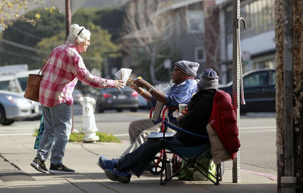 Kathy Beitscher of San Diego purchases a copy of the Street Spirit newspaper from vendors Donald and Joslyn Cistrunk in Berkeley, California, on Friday December 30, 2016. Sally Hindman and the Youth Spirit Artworks nonprofit she runs will be taking over the Street Spirit homeless newspaper on January 1st. The paper has been in existence for 22 years, and the youth organization's involvement will infuse a youthful new look to the publication.