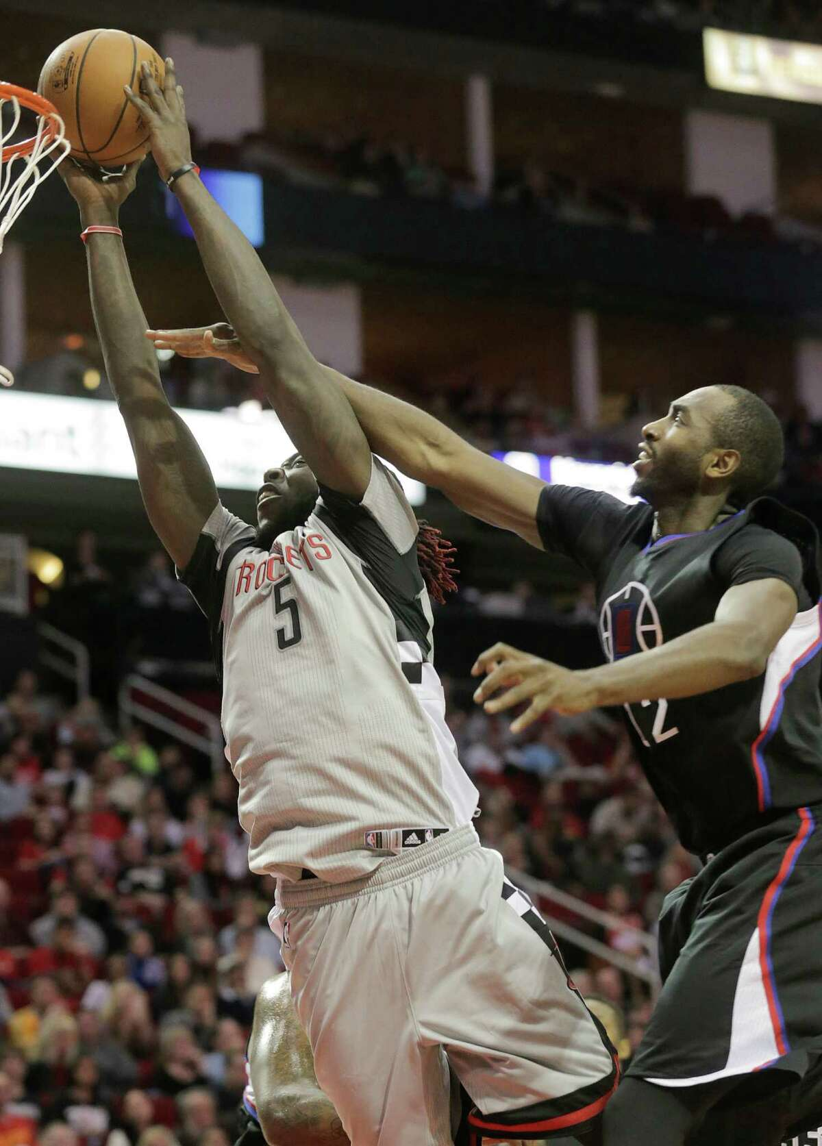 Rockets forward Montrezl Harrell, left, is not deterred by Clippers forward Luc Mbah a Moute's foul as he surges to the rim Friday. Harrell came off the bench and had 29 points on 10-for-14 shooting.