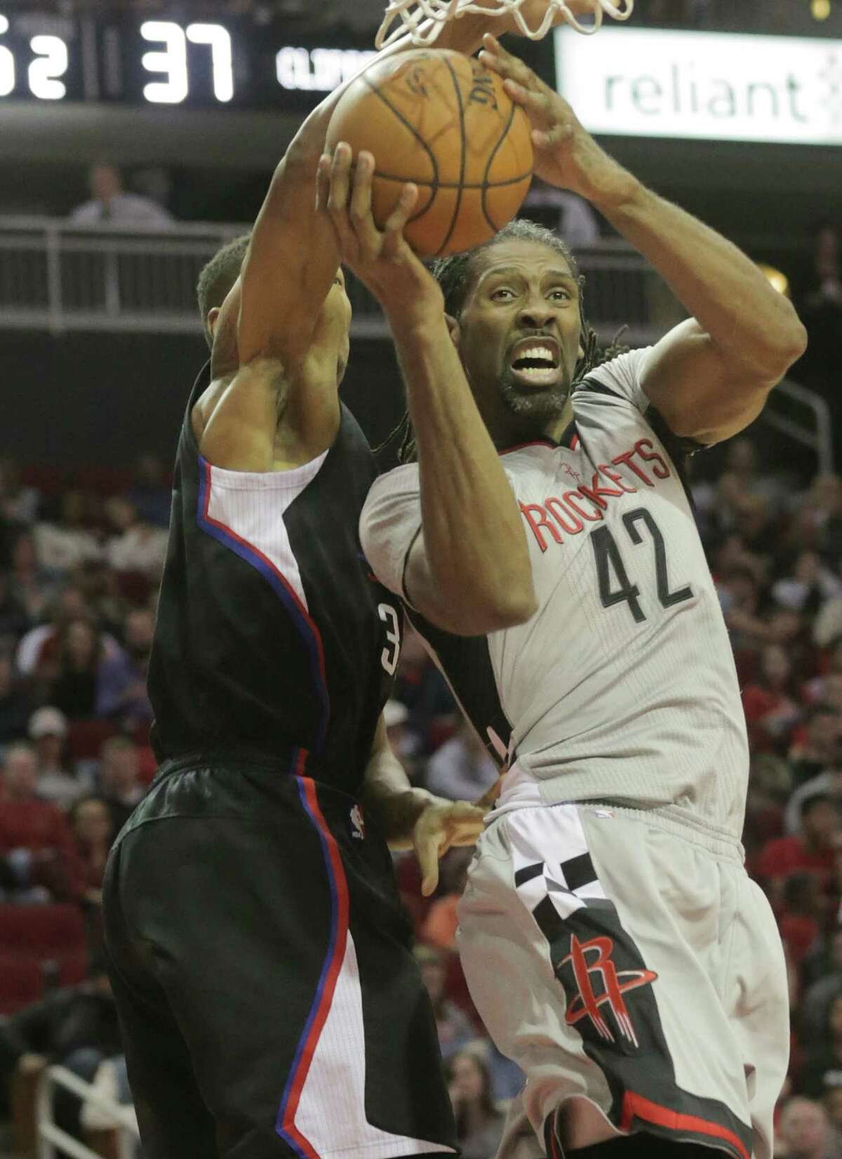 Rockets center Nene gets tied up under the basket by a determined Clipper.