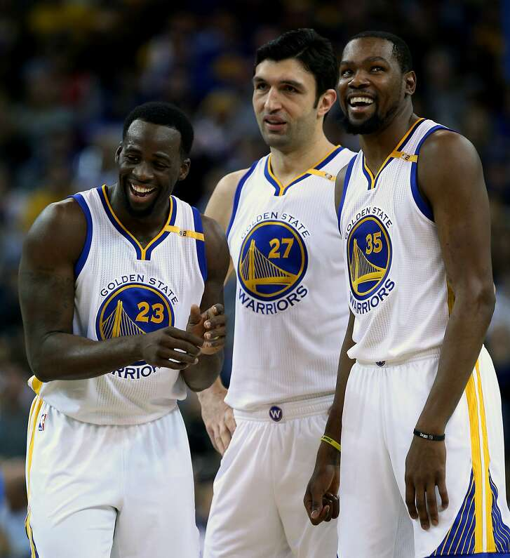 Golden State Warriors Draymond Green (23), Zaza Pachulia (27) and Kevin Durant (35) react after Golden State Warriors guard Stephen Curry (30) gets fouled during the first half of an NBA basketball game between the Golden State Warriors and the Dallas Mavericks at Oracle Arena on Friday, Dec. 30, 2016 in Oakland, Calif. The Warriors lead 59-48 at half time.